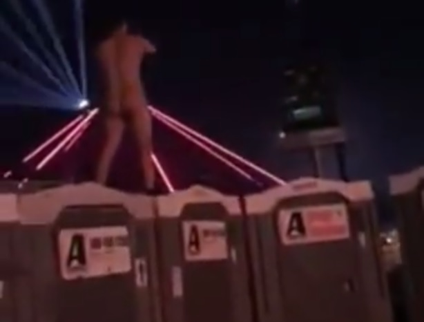 naked dude jumps off festival toilets